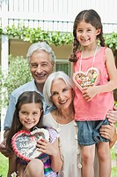 Germany, Bavaria, Grandparents with granddaughter holding gingerbread, smiling, portrait