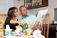 Kenyan couple reading paper at breakfast time, Nairobi, Kenya