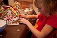 Young girl decorates a gingerbread house at a kitchen table
