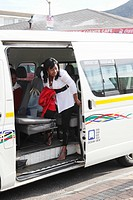Woman getting out of taxi, Fish Hoek, Cape Town, Western Cape Province, South Africa