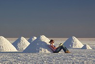 A tourist relaxes amongst the salt heaps near Colchani, Salar de Uyuni, Bolivia, South America