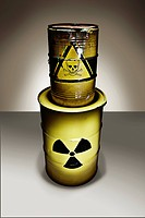 Studio shot of metal barrels with radiation warning sign