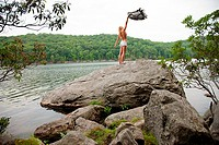 Young woman holding blanket on rock at lake