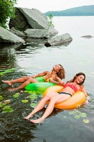 Young women floating on lake with inflatable rings