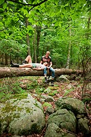 Couple relaxing together on log in forest (thumbnail)
