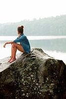 Young woman sitting on rock overlooking lake