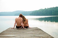 Couple sitting on pier looking over lake