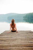 Young woman sitting on pier looking at lake