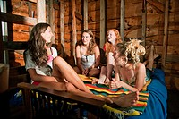 Teenage girls chilling out together on bed in boat house (thumbnail)