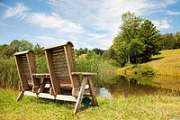 A double wooden chair positioned by a lake