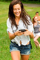 Teenage girl looking at mobile phone while walking in countryside with friends