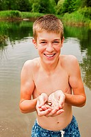 Teenage boy holding small reptile in hands by lake