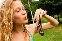 Teenage girl holding small snake