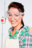 Female carpenter wearing safety glasses in workshop, portrait (thumbnail)