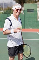 Older man drinking lemonade on court