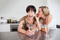 Laughing women whispering in kitchen