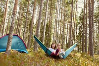 Women relaxing in hammock at campsite