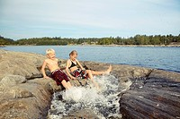 Children splashing in rocky lake
