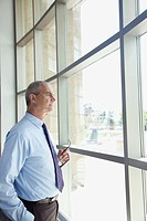 Portrait of businessman looking through window