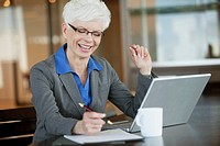 Portrait of smiling businesswoman working at desk in office