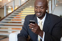 Portrait of smiling businessman texting on cell phone