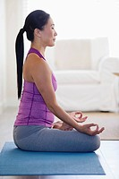 Mid adult woman meditating at home