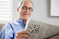 Smiling middle_aged man reading newspaper on sofa