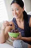 Smiling woman eating cherries