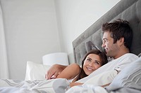 Couple lying in bed in morning