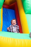 Boy sliding down an inflatable ride