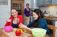 Girls peeling vegetables in kitchen