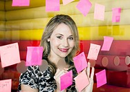 Businesswoman sticking notes on window