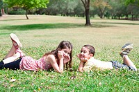 Cute children lie down on green grass