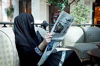 United Arab Emirates, Dubai, Arab Woman in a Hijab Reading Newspaper                                                                                  ...