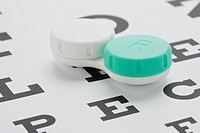 Contact lenses in case on eye chart, studio shot