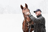 USA, Illinois, Metamora, Smiling mature man with horse during blizzard
