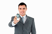 Smiling businessman showing his phone against a white background
