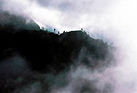 An overview of a mountain ridge with swirling clouds.