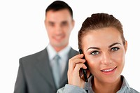 Close up of businesswoman on the phone with colleague behind her against a white background