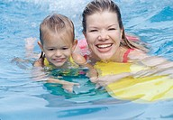 Mother and young daughter in swimming pool.