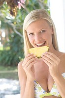 Young woman in bikini eating pineapple                                                                                                                ...