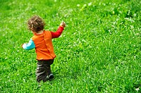 A one year old baby girl playing in a green meadow