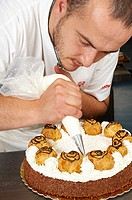 A pastry chef decorating a cake with whipped cream