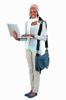 Side view of female student in winter clothing and laptop against a white background