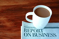 Coffee cup and business section of newspaper on desk.