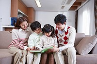 Happy family reading a book on the sofa
