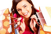 Portrait of happy girl with colorful paper bags looking at camera with smile
