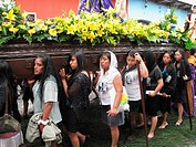 Group of young women carrying float of the Virgin Mary during Holy Week