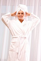Portrait of pretty female in white bathrobe with towel on head