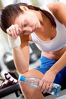 Portrait of tired brunette with bottle of water in hand having rest after workout